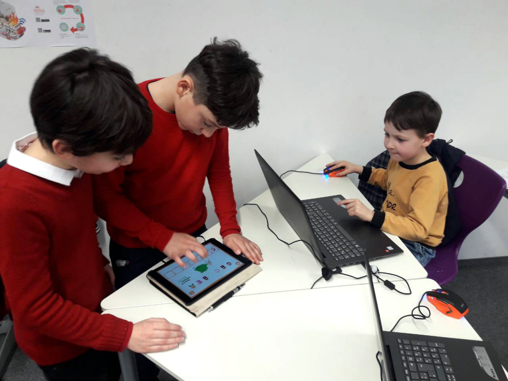 Children playing with an educational app on a tablet.