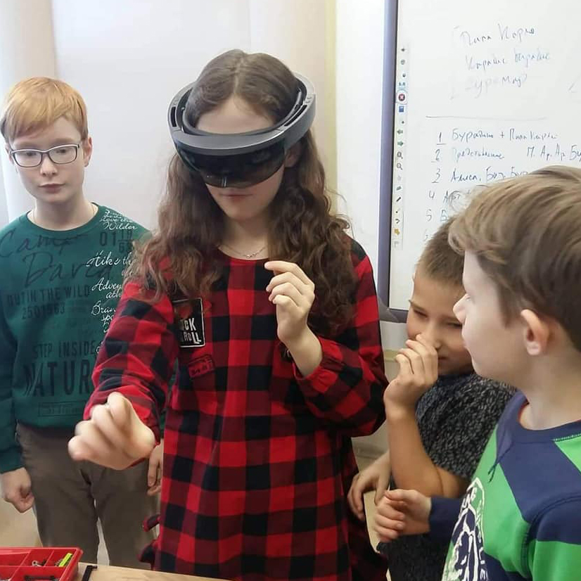 Children use a VR headset to play a game.